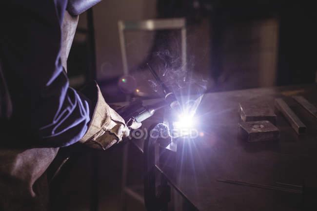 Schweißerin arbeitet in der Werkstatt an einem Metallstück — Stockfoto