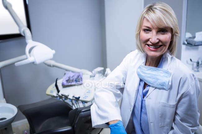 Ritratto di dentista sicuro seduto accanto alla sedia presso la clinica dentistica — Foto stock