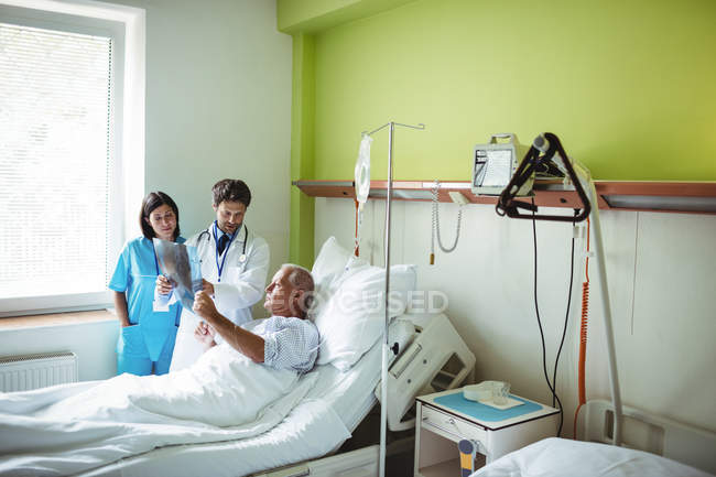 Doctor and nurse interacting over x-ray report with patient in hospital — Stock Photo