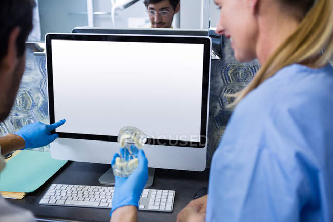 Dentist and dental assistant using computer while working on mouth model — Stock Photo