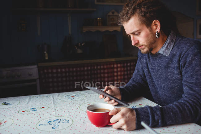 Hipster using digital tablet while having tea at home — Stock Photo