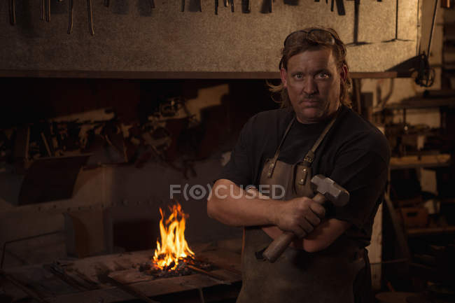Portrait of blacksmith with arms crossed and holding hammer at work shop — Stock Photo
