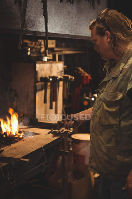 Blacksmith heating metal piece in blacksmiths fire at workplace — Stock Photo