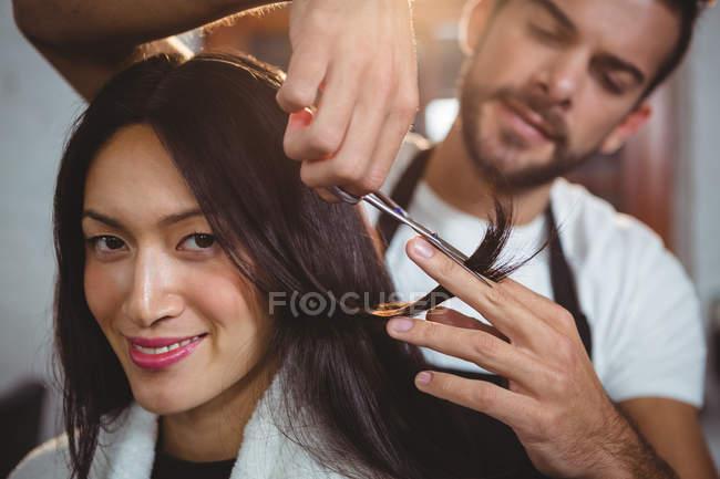 Donna ottenere i capelli tagliati con le forbici in salone — Foto stock