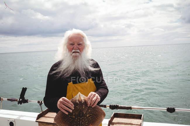 Porträt eines Fischers, der Rochenfische auf einem Boot hält — Stockfoto
