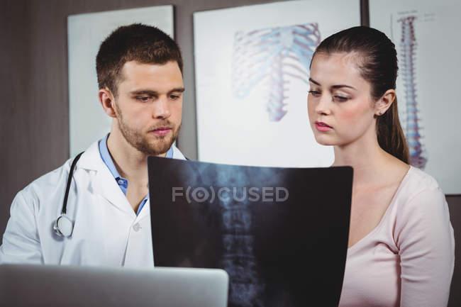 Fisioterapista che spiega la radiografia della colonna vertebrale alla paziente in clinica — Foto stock