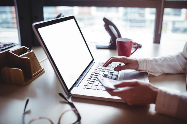 Image recadrée de femme d'affaires tenant le téléphone mobile et utilisez l'ordinateur portable au bureau — Photo de stock