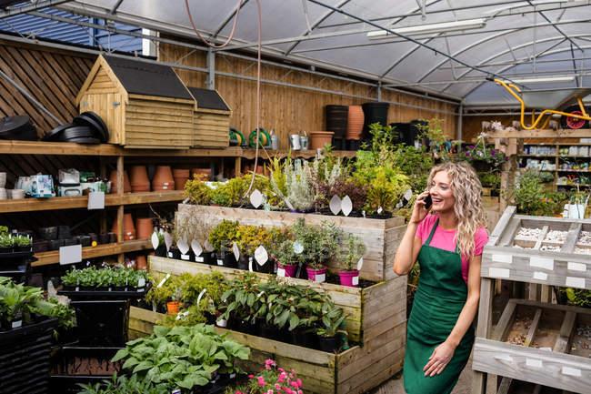 Женщины флорист, говоря на мобильном телефоне в садовом центре — стоковое фото