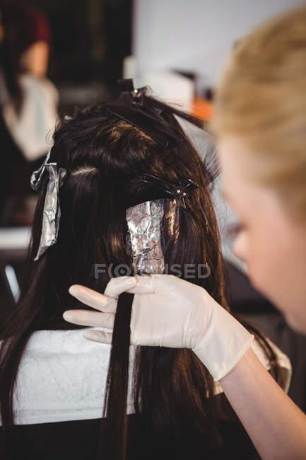 Parrucchiere femminile tintura dei capelli del suo cliente nel salone — Foto stock