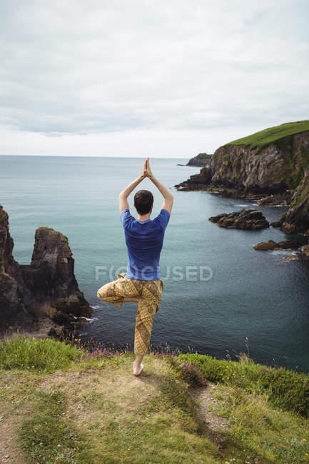 Задний вид человека, занимающегося йогой на скале — стоковое фото