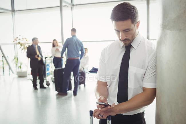Pilote utilisant un téléphone portable dans la zone d'attente au terminal de l'aéroport — Photo de stock