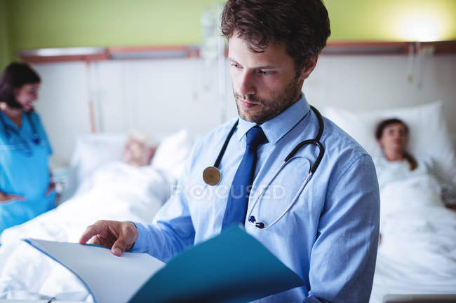 Doctor checking report in hospital ward — Stock Photo