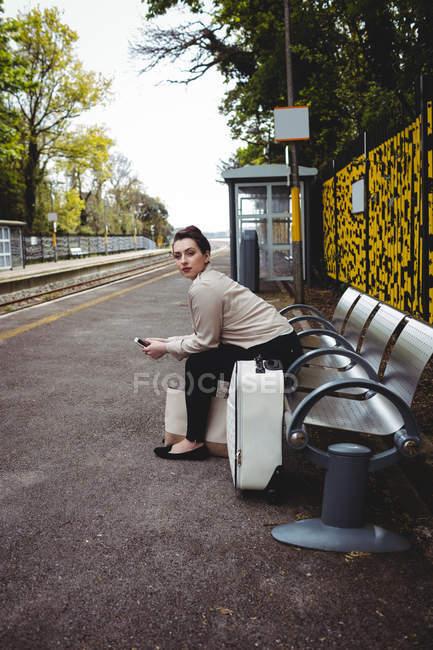 Belle femme assise sur un banc au quai de la gare — Photo de stock