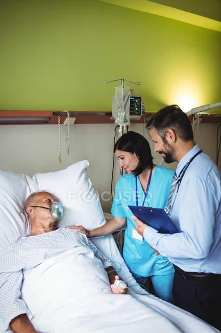 Krankenschwester tröstet Seniorin mit Arzt im Krankenhaus — Stockfoto