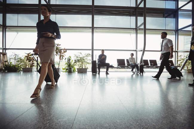 Деловые люди прогуливаются с багажом в терминале аэропорта — стоковое фото