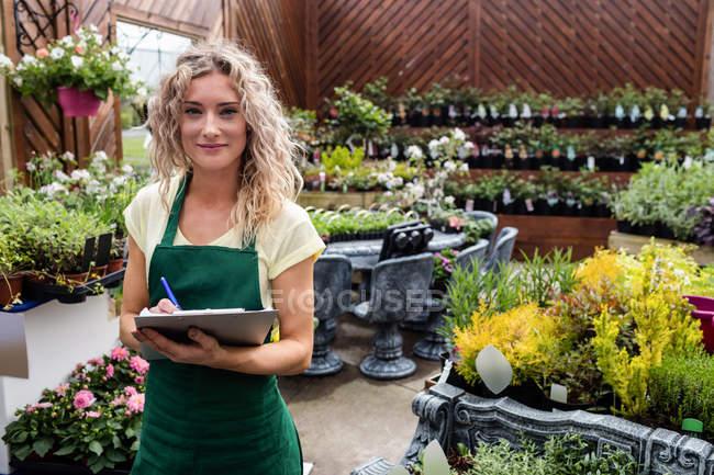 Портрет жіноче флорист дати з буфера обміну в садовому центрі — стокове фото
