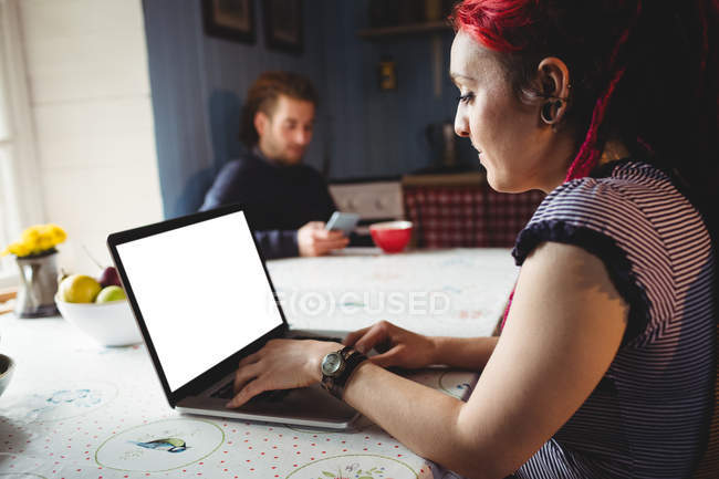 Hipster woman using laptop while man sitting in background at home — Stock Photo