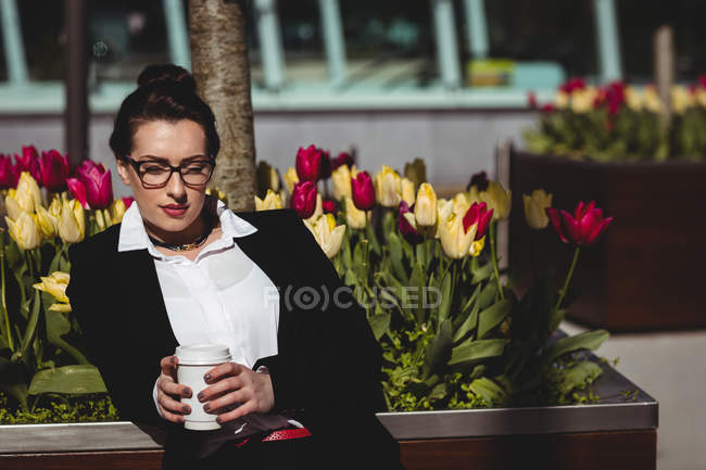 Businesswoman with disposable coffee cup against flowers — Stock Photo