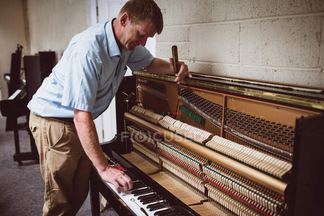 Piano technician repairing wooden piano at workshop — Stock Photo