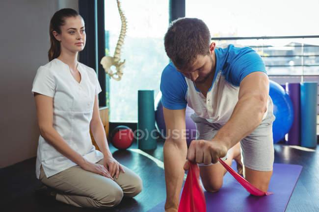 Женщина-физиотерапевт помогает пациенту-мужчине во время тренировки в клинике — стоковое фото