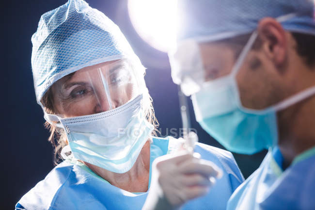 Smiling surgeons interacting in operation room at hospital — Stock Photo