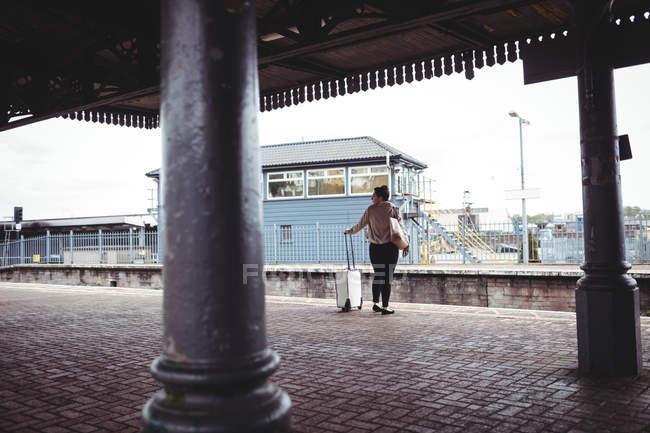 Vue arrière de la femme debout au quai de la gare — Photo de stock