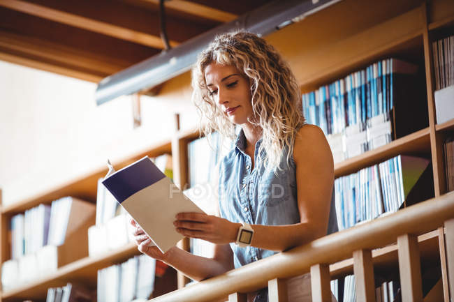 Чудова жінка читає в бібліотеці. — стокове фото
