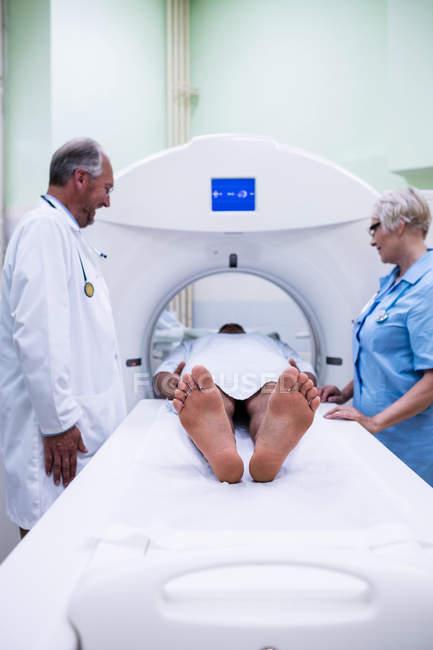 Patient en entrant dans la machine IRM avec des médecins à l'hôpital — Photo de stock