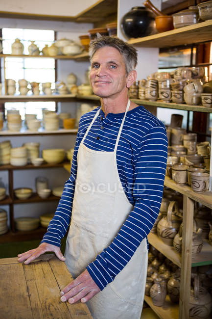 Portrait of happy male potter standing in pottery workshop — Stock Photo