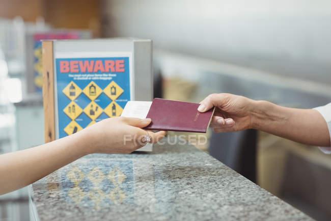 Línea aérea llegadas asistente dando pasaporte a pasajero en el mostrador de facturación de aeropuerto - foto de stock