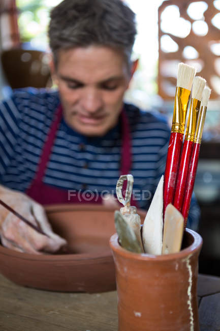 Close-up of paintbrush and work tool in pot with potter working on background — Stock Photo