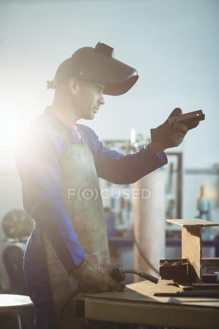 Schweißer begutachtet Metallstück in Werkstatt — Stockfoto