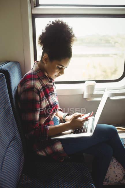 Вид збоку жінки, використовуючи телефон з ноутбуком, сидячи в поїзді — стокове фото