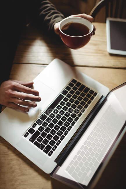 Vue grand angle de l'homme en utilisant un ordinateur portable à la table — Photo de stock