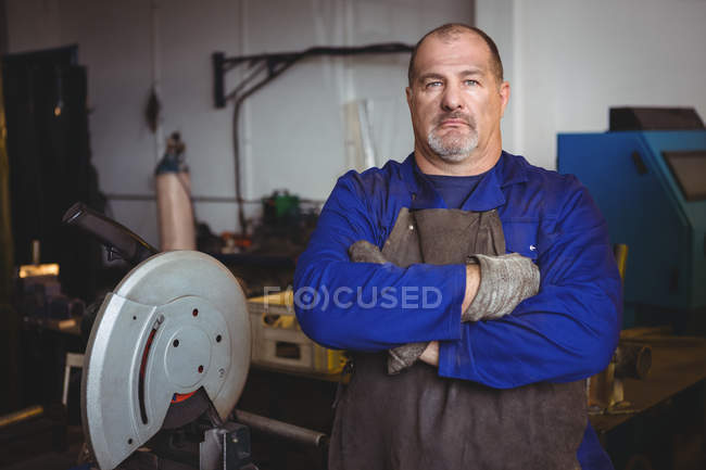 Portrait of welder standing with arms crossed in workshop — Stock Photo