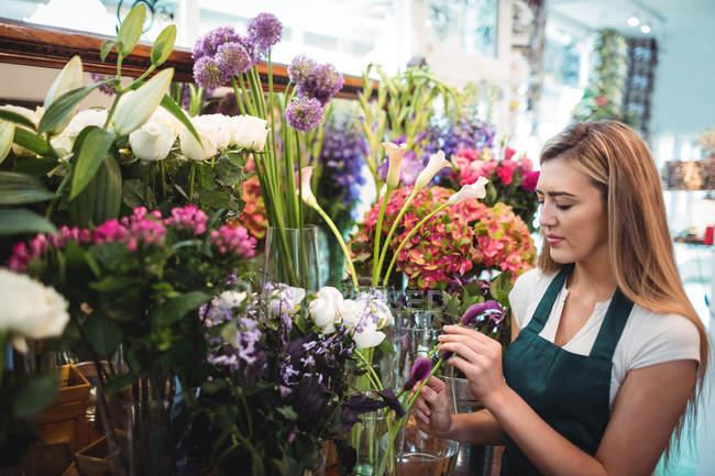Цветочница собирает цветы в цветочном магазине — стоковое фото