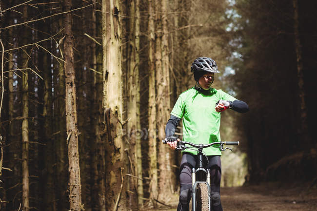 Mountain biker checking time while riding in forest — Stock Photo