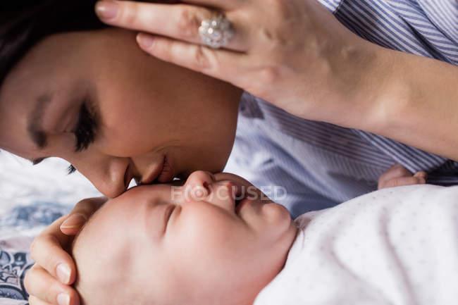 Madre besando a su bebé en la frente mientras él duerme en la sala de estar en casa - foto de stock