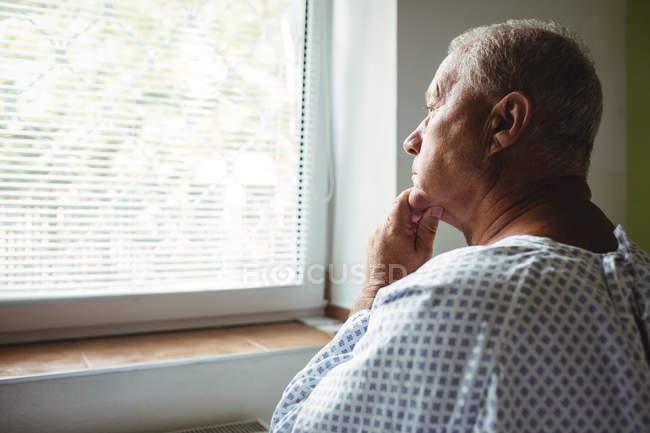 Старший мужчина в задумчивом настроении смотрит в окно больницы — стоковое фото