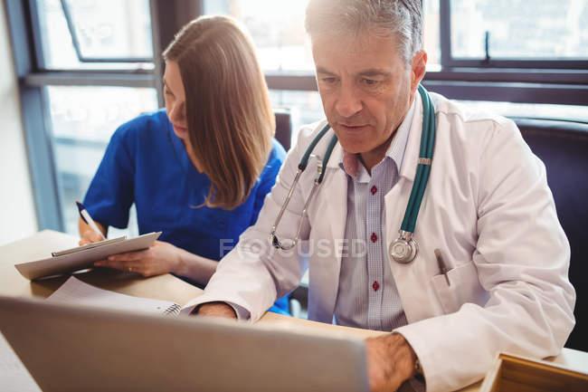 Врач обсуждает с медсестрой за ноутбуком в больнице — стоковое фото