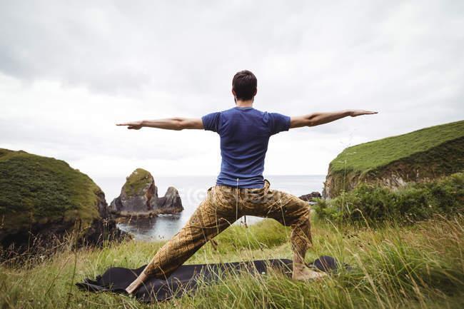 Vista posteriore dell'uomo che esegue esercizio di stretching sulla scogliera — Foto stock