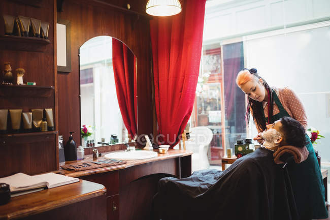 Man getting his beard shaved with shaving brush in barber shop — Stock Photo