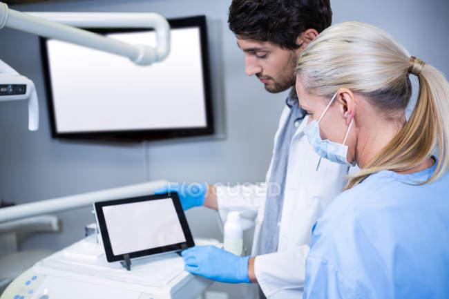 Zahnarzt und Zahnarzthelferin arbeiten an digitalem Tablet in Zahnklinik — Stockfoto
