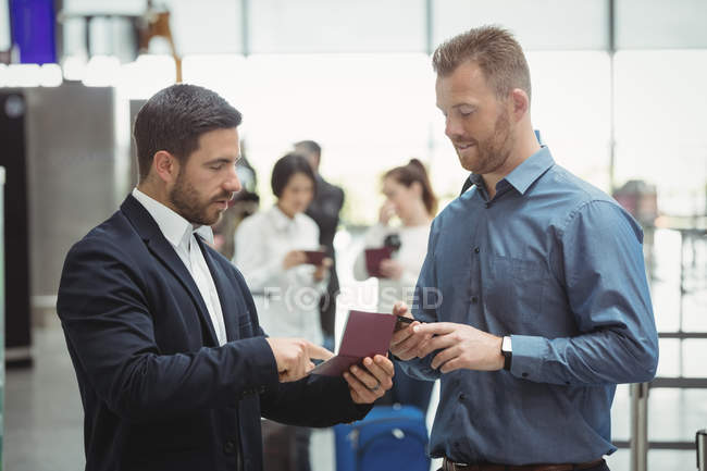 Business people checking their passport in airport terminal — Stock Photo