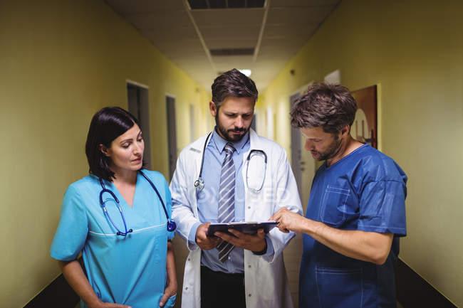 Arzt interagiert über Bericht mit Stationsjunge und Krankenschwester im Krankenhausflur — Stockfoto