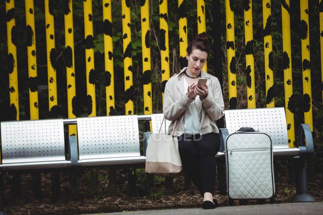 Jeune femme utilisant un téléphone portable assis sur un banc à quai de la gare — Photo de stock