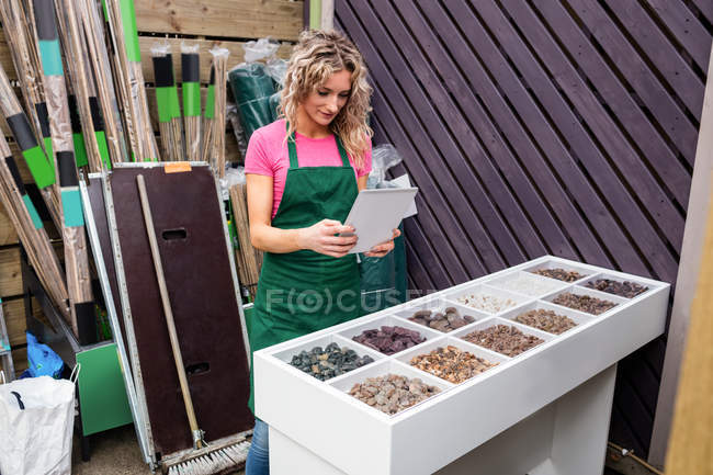 Female florist photographing pebbles in garden centre — Stock Photo