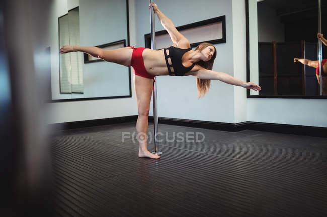 Танцовщица на шесте практикует танец в фитнес-студии — стоковое фото