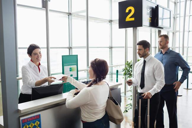 Mulher dando o seu passaporte para a companhia aérea entrada atendente no balcão do check-in de aeroporto — Fotografia de Stock