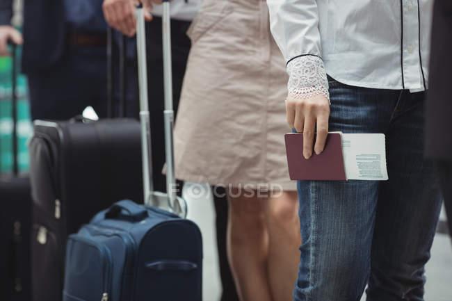 Пасажири проведення паспортів та інтернатних пройти очікування в черзі всередині аеропорту терміналу — стокове фото